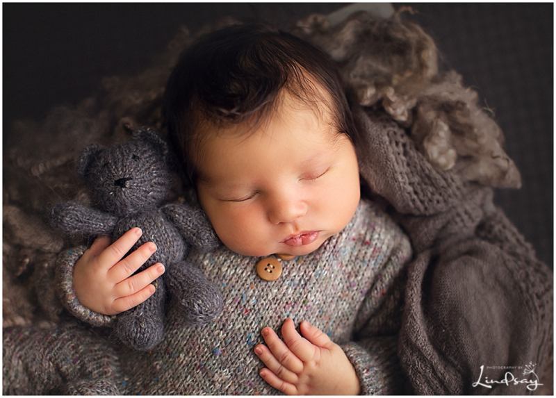 Close up image of newborn boy asleep while holding knit teddy bear while at photography by Lindsay studio.
