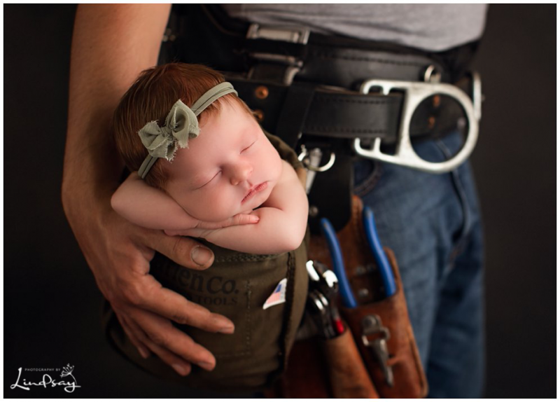 Newborn asleep in dads lineman belt pocket while at Photography by Lindsay studio.