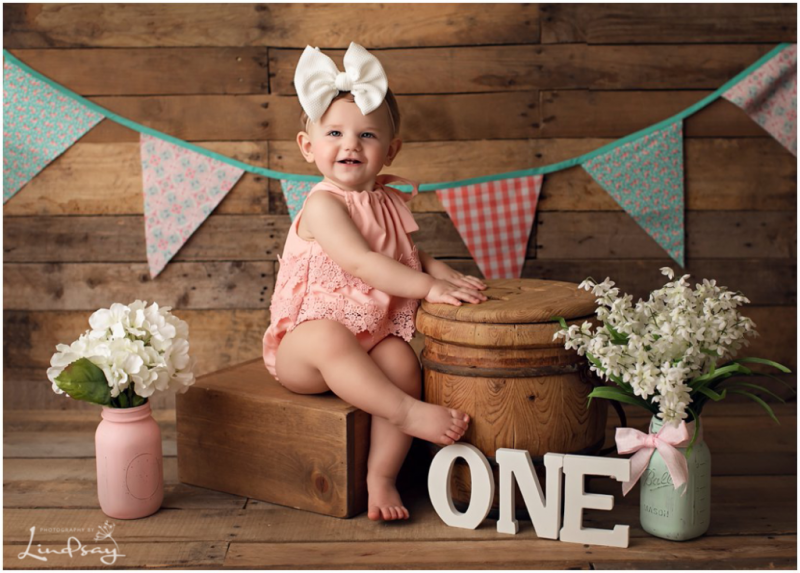 Baby girl smiling and playing with props while at Photography by Lindsay studio.