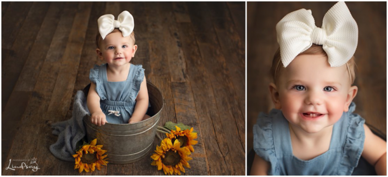 12 month old baby sitting in a bucket while wearing denim romper and smiling at the camera at Photography by Lindsay studio.