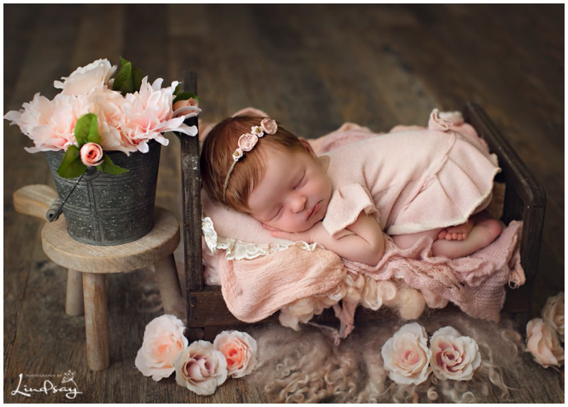 Newborn girl asleep on small wooden bed taken by best local newborn photographer, Photography by Lindsay.